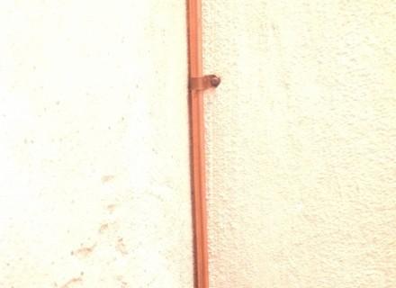 Particolare tubazione e fissaggio a parete artigianale in rame