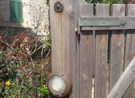 Particolare pulsante campanello in ottone e lampada in Cortem con tubazione in rame su trave cancello in legno